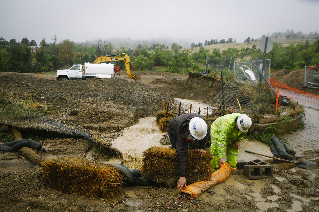 Workers tried to clear some of the drainage that became clogged after the flash flood in Boulder, CO.