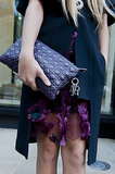 A richly hued Dior clutch echoed the eggplant palette of her ensemble.