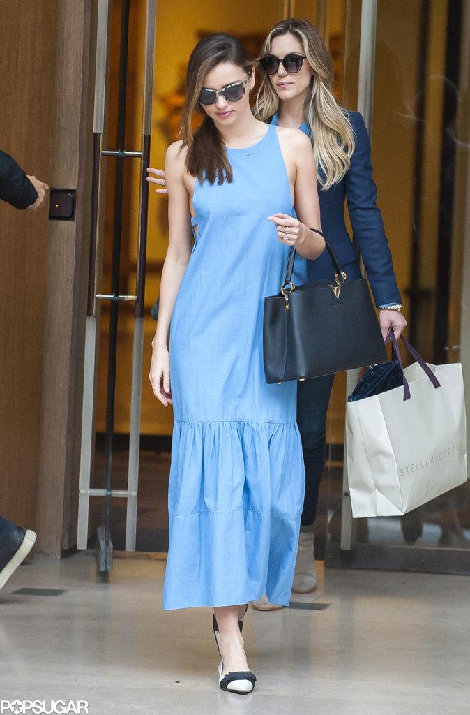 Miranda Kerr popped in a blue maxi dress and a black structured Louis Vuitton purse in Paris.