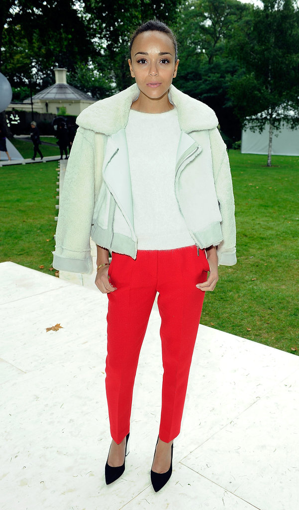At the Topshop Unique Spring 2014 show in London, Ashley Madekwe styled herself in a Topshop Unique shearling jacket, red Topshop trousers, and black pumps, also by Topshop.