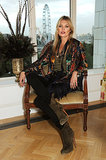 Kate Moss sat in a velvet chair.