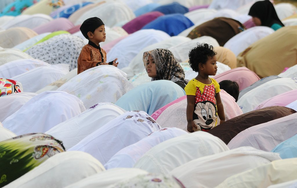 Kids played while thousands prayed for Eid al-Adha in Surabaya, Indonesia.