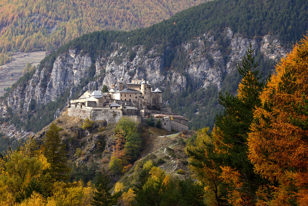Queyras Castle in the French Alps was surrounded by green and golden trees.