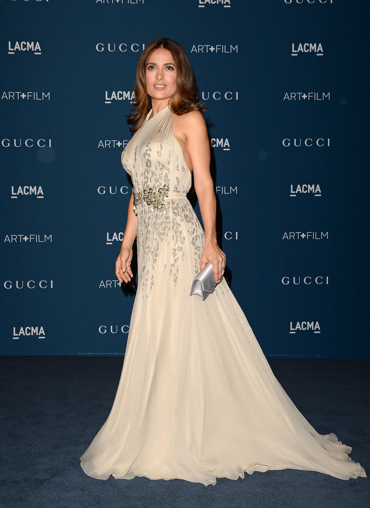 Salma Hayek looked glamorous in a figure-flattering Champagne Gucci gown, a silver clutch, and diamonds by Harry Winston.