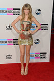 Golden girl Taylor Swift looked every bit the pop princess that she is posing in a glistening Julien MacDonald mini, strappy Jimmy Choos, and Lorraine Schwartz jewels.