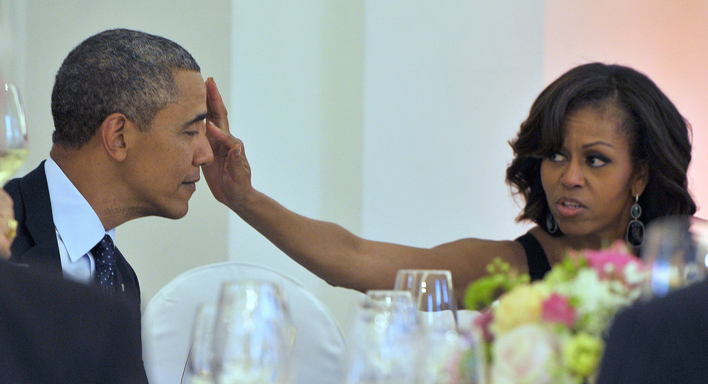 Michelle affectionately wiped something off her husband's face during an official dinner in Berlin.