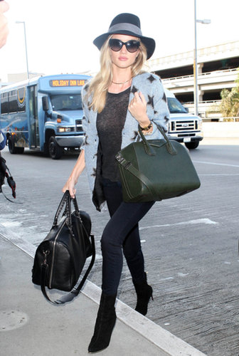 How does Rosie Huntington-Whiteley arrive curbside? With sunglasses, a wide-brimmed hat, and not one but two luxe bags.