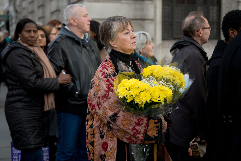 A woman held a bouquet of flowers while waiting to pay her respects in London.
