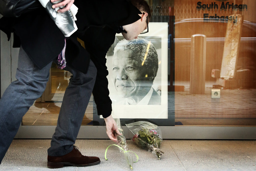 A man set flowers beneath a photo of Mandela in Belgium.