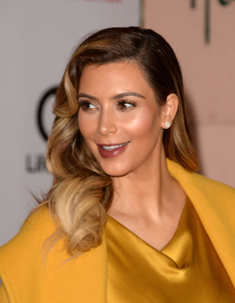 Kim Kardashian smiled on the red carpet as her fiancé, Kanye West, waited for her nearby.