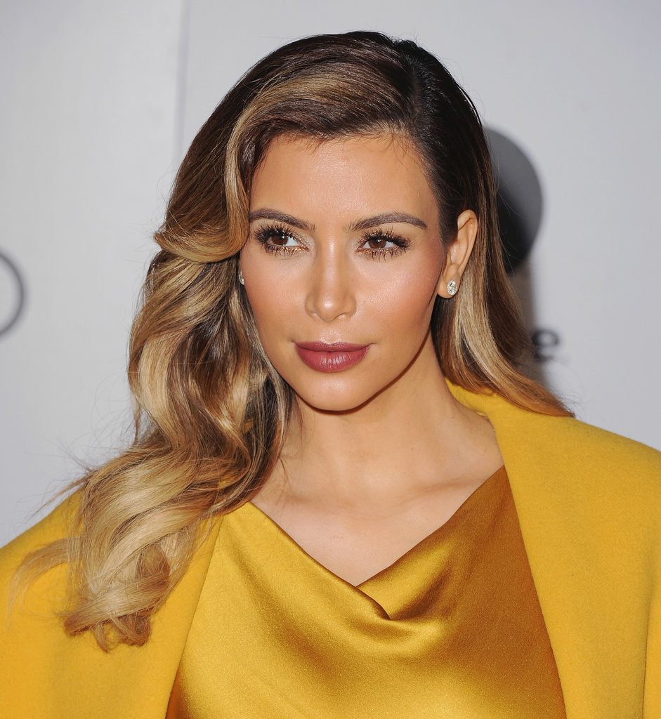 Kim Kardashian paired Old Hollywood glam waves with a festive gilded eyeliner and a berry-stained lip.