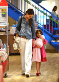 Working her wide-leg white denim with a chambray shirt while shopping with Suri in August 2012.