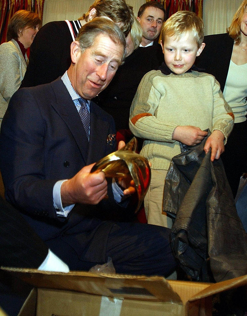 Prince Charles opened up a gift at a reception for children suffering from cancer and leukemia at Clarence House on Dec. 11, 2003.