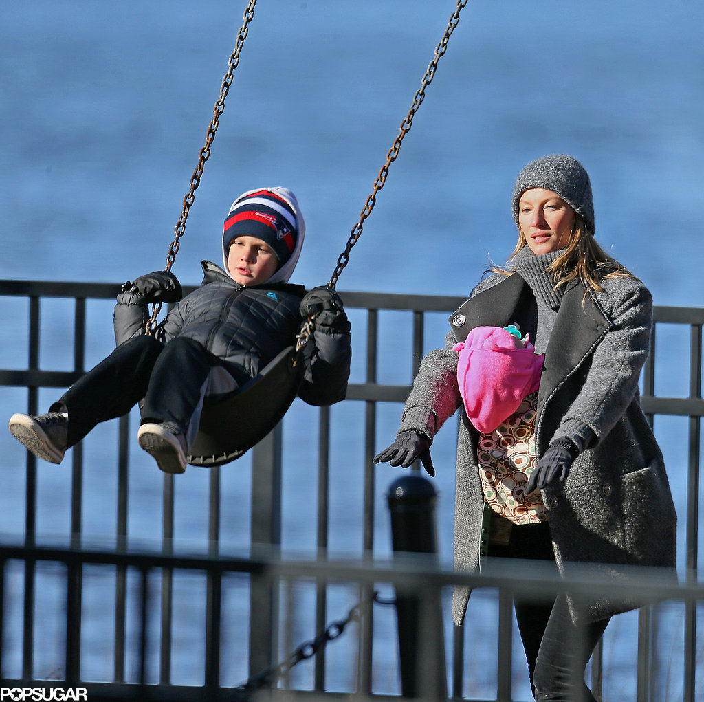 Gisele held Vivian and pushed Jack on the swings.