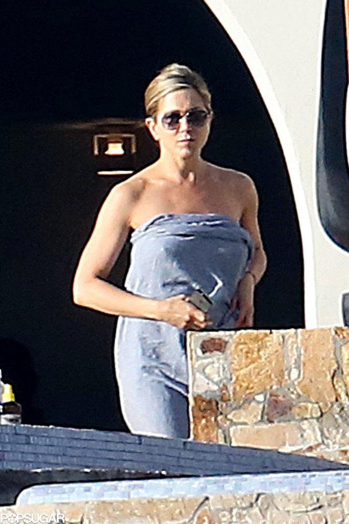 Jennifer wore a bikini beneath a large towel.