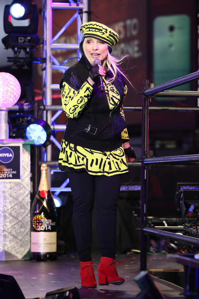 Debby Harry performed in a mostly black outfit punctuated by a printed yellow top and matching hat.