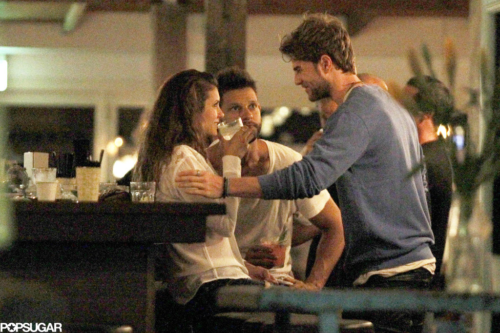 Nathaniel touched Nina's arm at the bar.