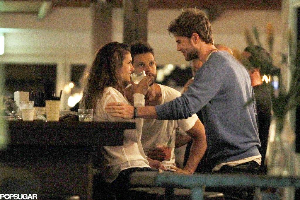 Nathaniel touched Nina's arm at the bar.