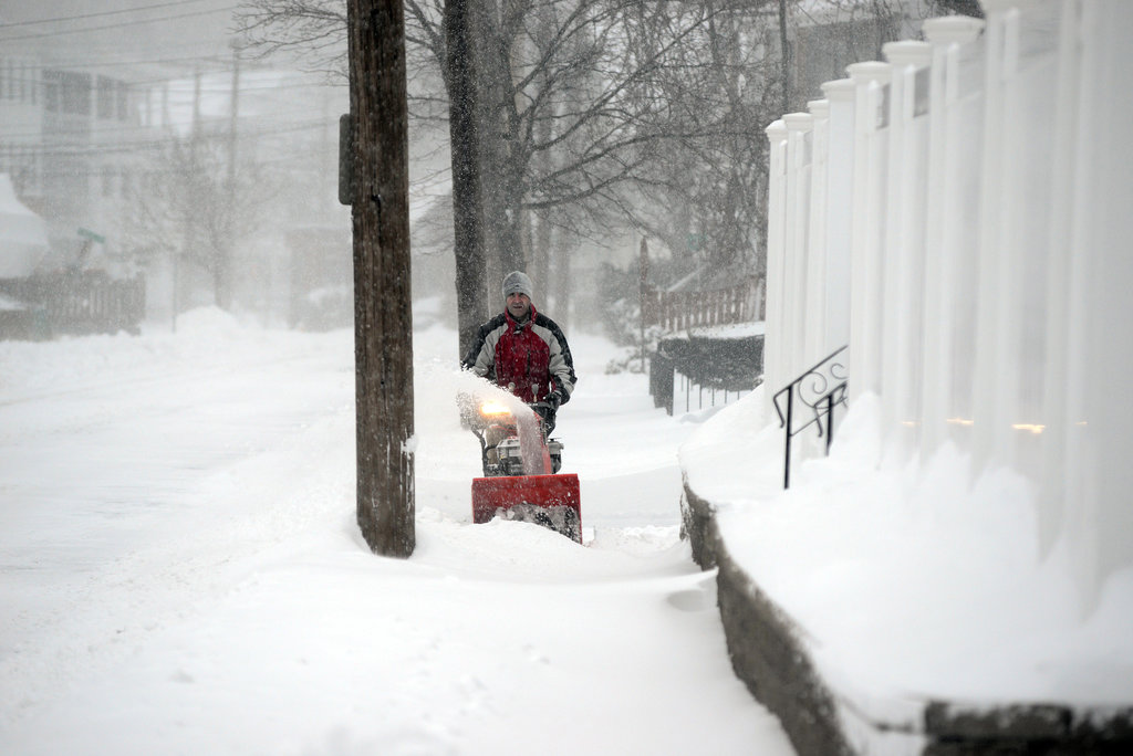 After the overnight storm in Winthrop, MA, a man took to the sidewalk with his snowblower. The nearby city of Boston expected 10 to 19 inches by Friday night, just over 24 hours into the storm.