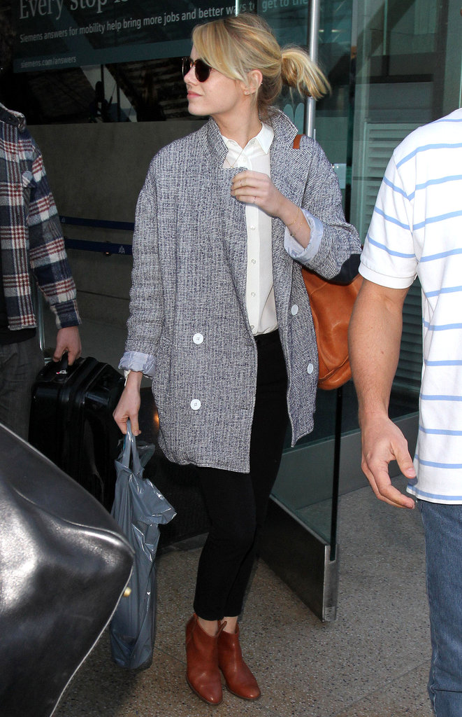 Forget traveling — we'd happily re-create Emma Stone's look for a day at the office! Black and brown work together perfectly when it comes to trousers and ankle boots, and her double-breasted jacket is a menswear-inspired update to the regular blazer.