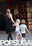 Angie held onto her twins' hands as they explored the park.