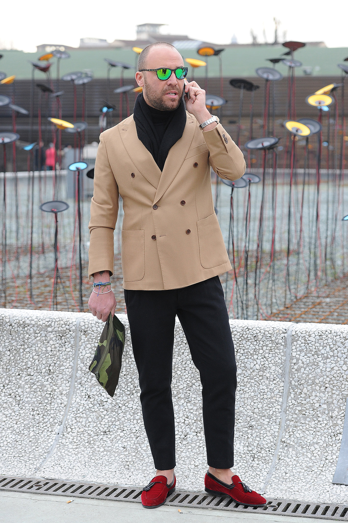We can't decide what we love more: the jacket, the shades, the clutch, or those shoes — this guy nailed it.
