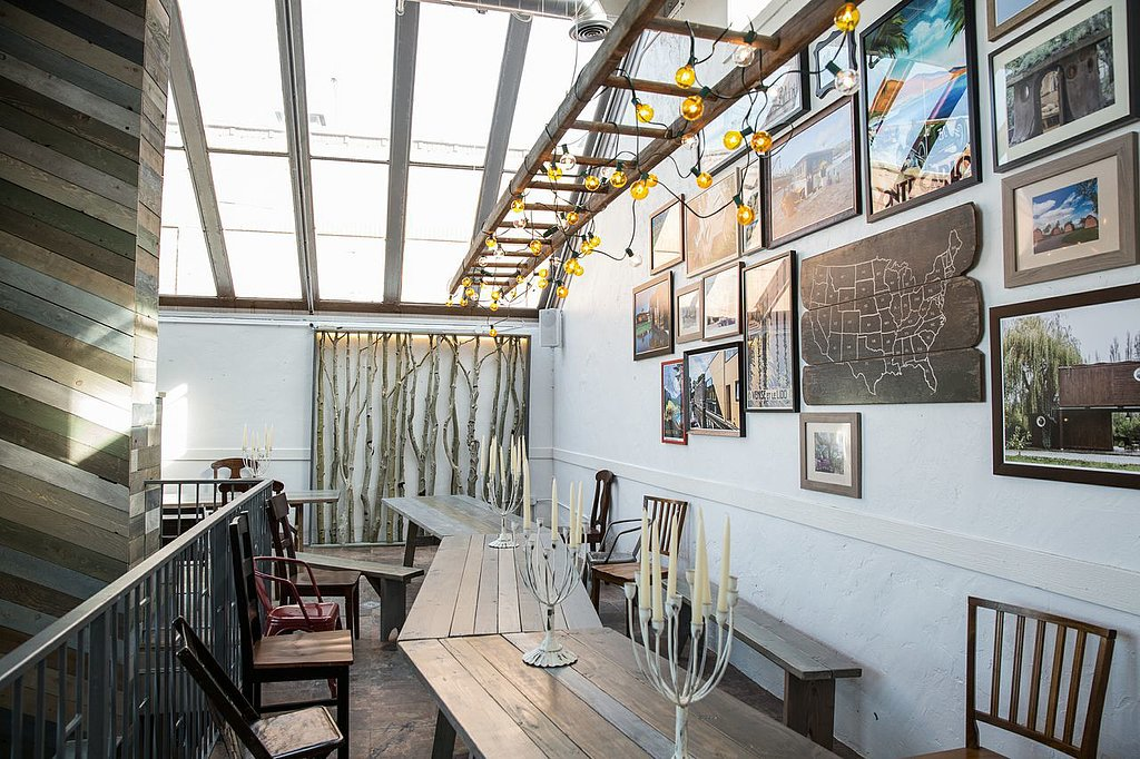 Since mingling is the main purpose of the Airbnb Haus, the banquet-style table is perfect for hosting dinners throughout the festival. The gallery wall is filled with cool finds, and the skylight windows keep the space light and airy.  Photo by Michael Friberg via Airbnb
