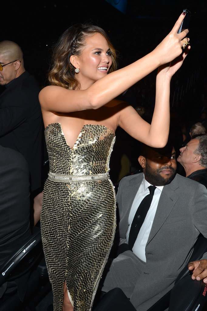 Chrissy Teigen stood up to snap a pic during the show.
