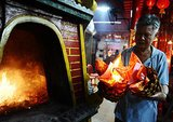 A man burned papers while praying at Hong San Ko Tee Temple in Surabaya, Indonesia.