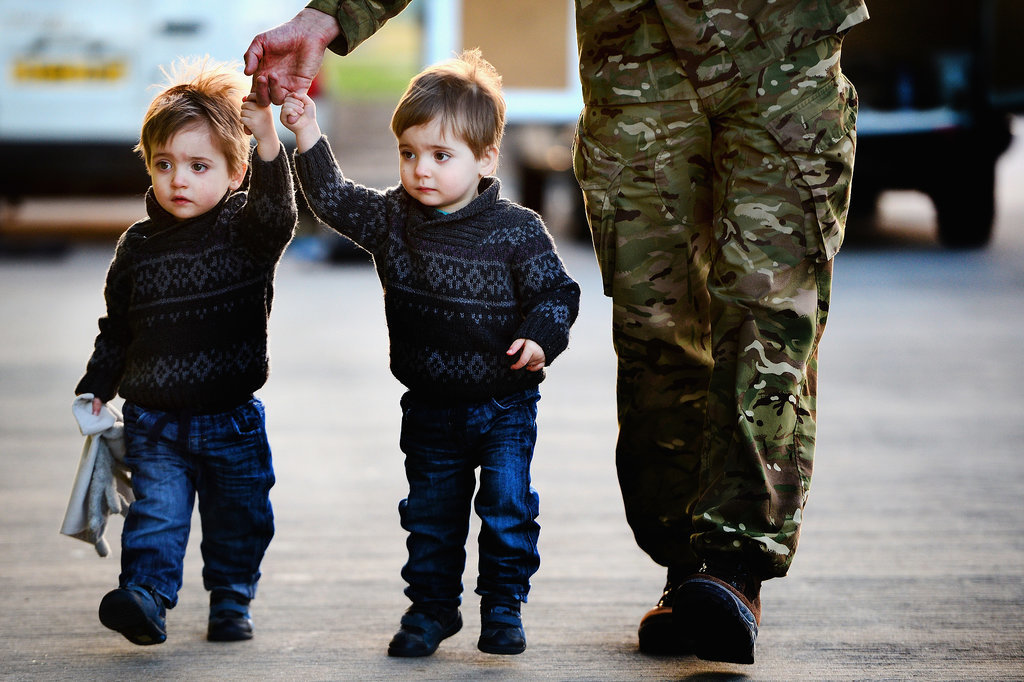 Two little boys held hands with their dad after he arrived.