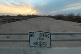 "A ""no diving"" sign sits over the dried-up Kern River in Bakersfield, CA."