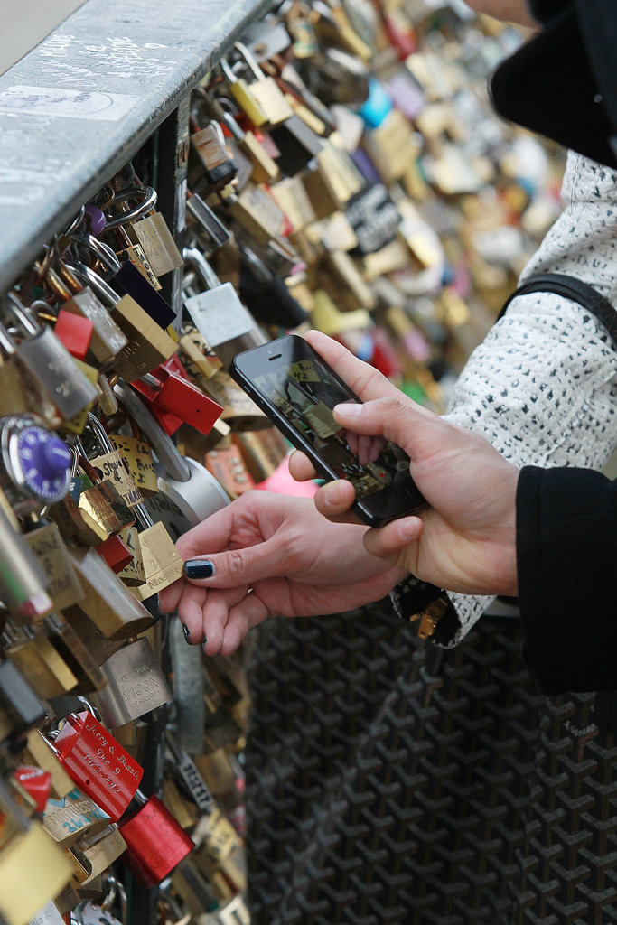 People take photos of padlocks on the Pont des Arts in Paris.
