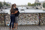 A couple embraces by their love lock in Paris.