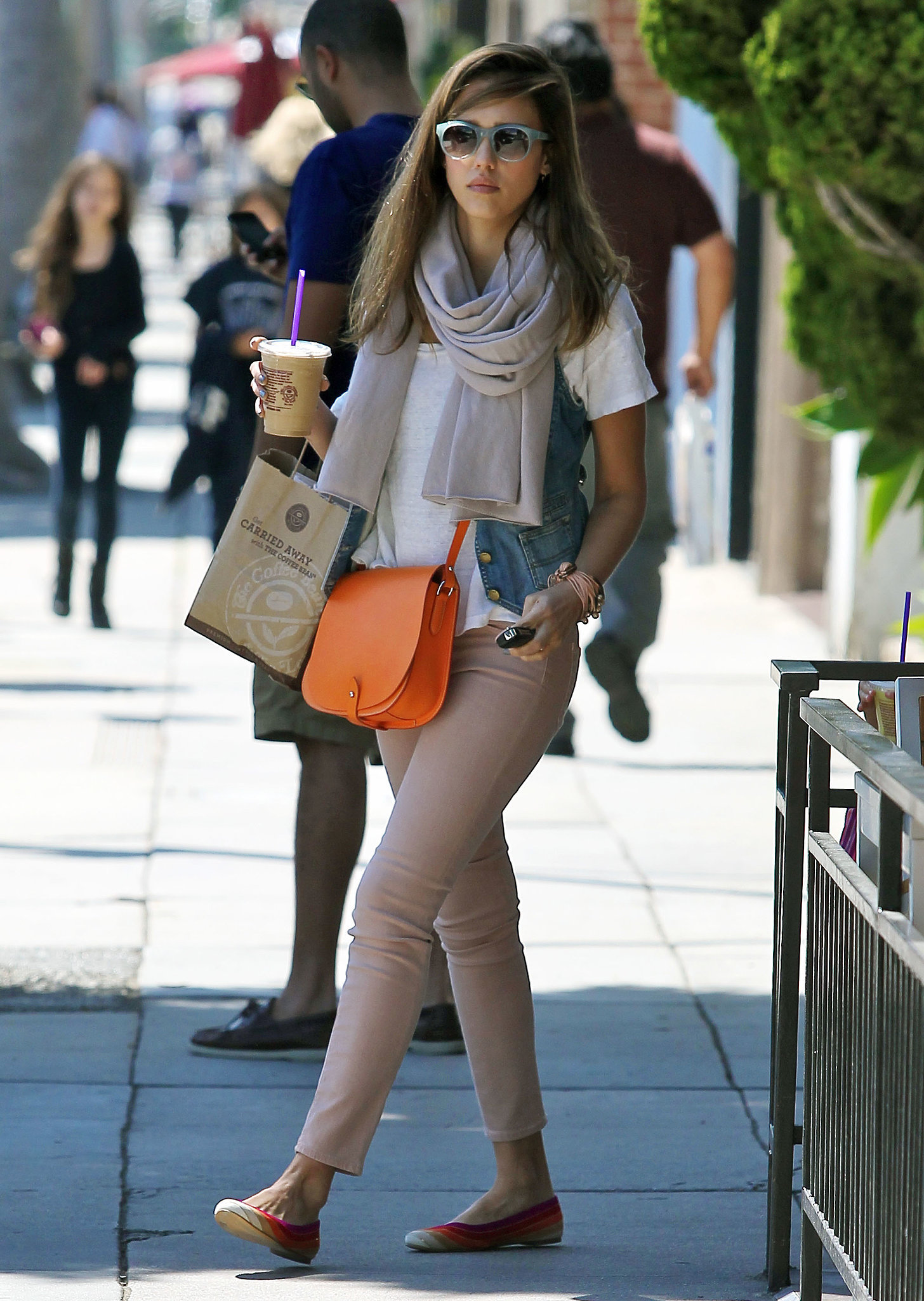 Jessica Alba injected a pop of pizzazz into her street style — a denim vest and rose-colored ankle jeans by J Brand — with a bright orange Ralph Lauren crossbody bag, multicolor Ferragamo flats, and blue Elizabeth and James shades while enjoying an iced coffee in Beverly Hills.