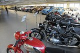 Several motorcycles sat beside the vintage car collection.