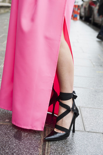 Strappy heels are an edgy contrast to a floor-length pink skirt.