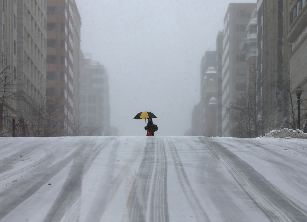A lone walker made their way across a snow-covered street in DC.