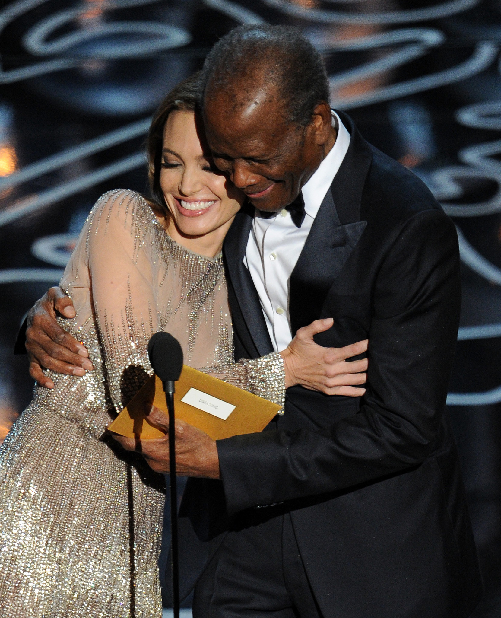 Angelina Jolie cuddled up to Sidney Poitier on stage as they presented the award for best director.