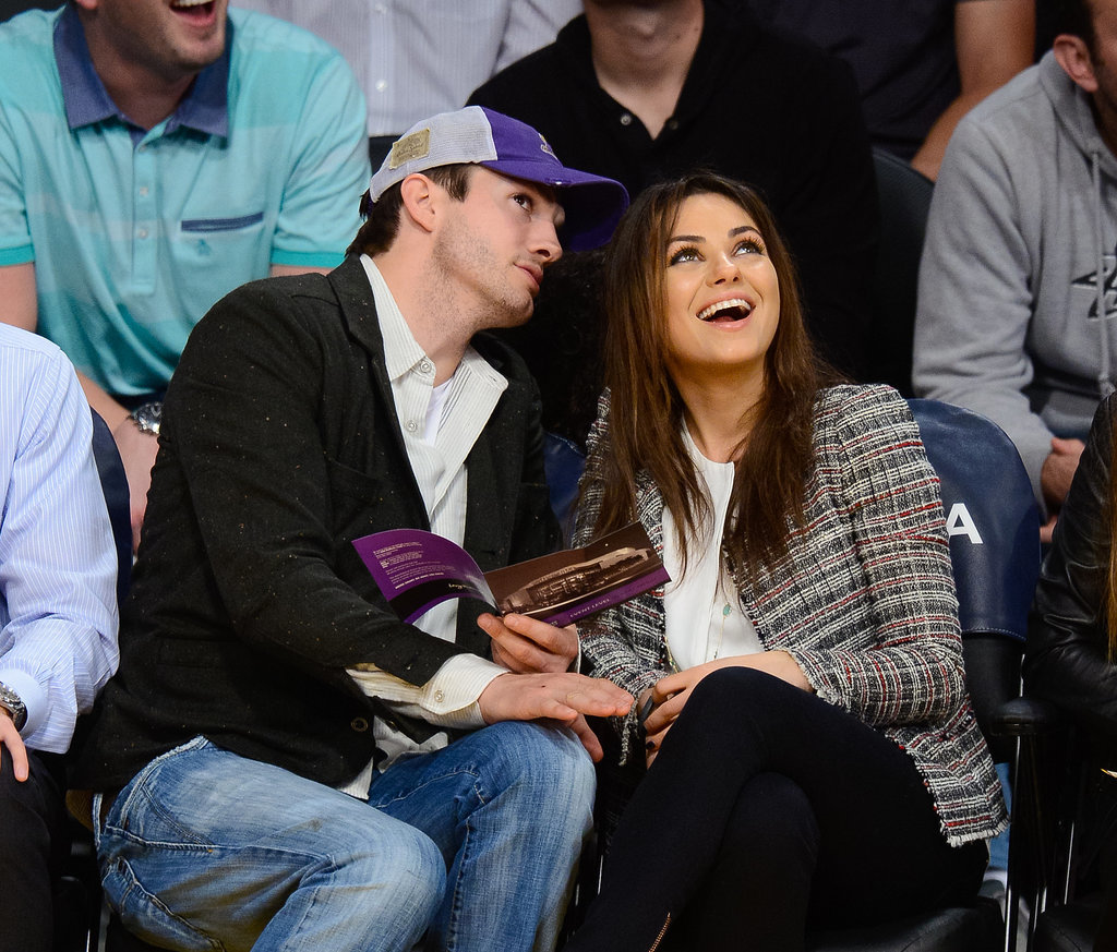 Mila Kunis and Ashton Kutcher got a little shy while showing PDA at a Lakers game in LA on Tuesday, eventually sharing