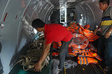 Personnel inspected life jackets on a search and rescue plane.