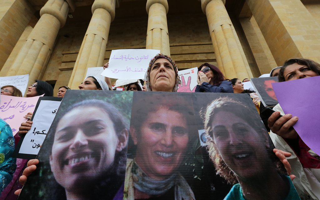 Women in Lebanon held up portraits of domestic-abuse victims.