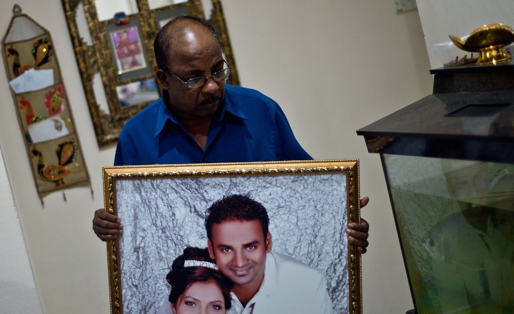 Subramaniam Gurusamy held a portrait of his son Puspanathan, one of the passengers on MH370.