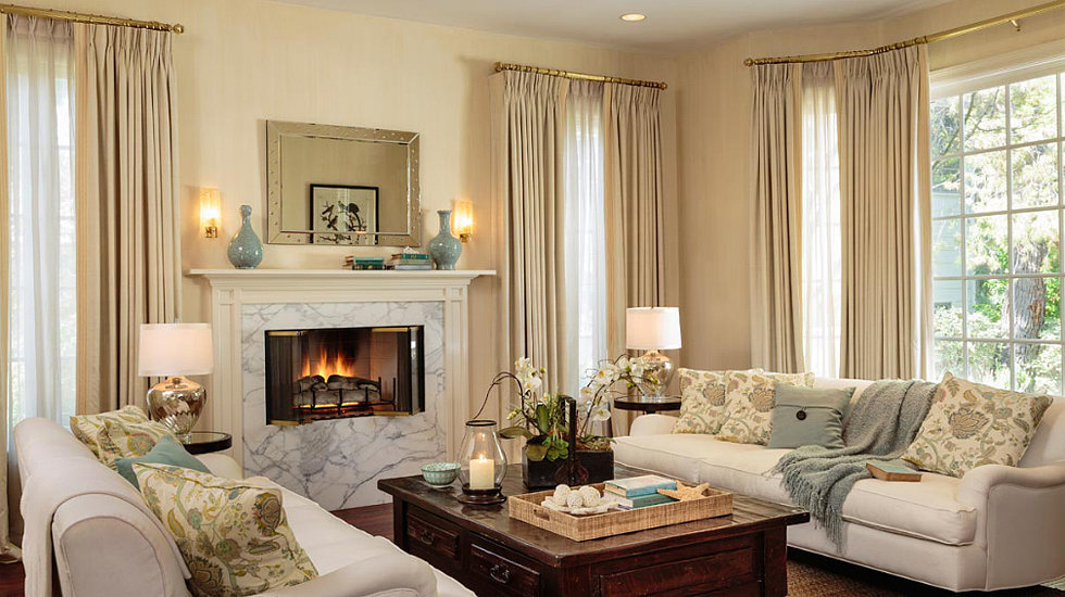 The living room's large windows, cream-and-aqua color palette, and fireplace give it a cozy yet elegant feel.   Source: Domaine Home