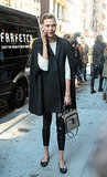 Karlie Kloss skipped a typical coat in favor of a poncho for a chilly NYC day. She wore it with a white long-sleeved top, cropped black skinnies, and basic ballet flats.