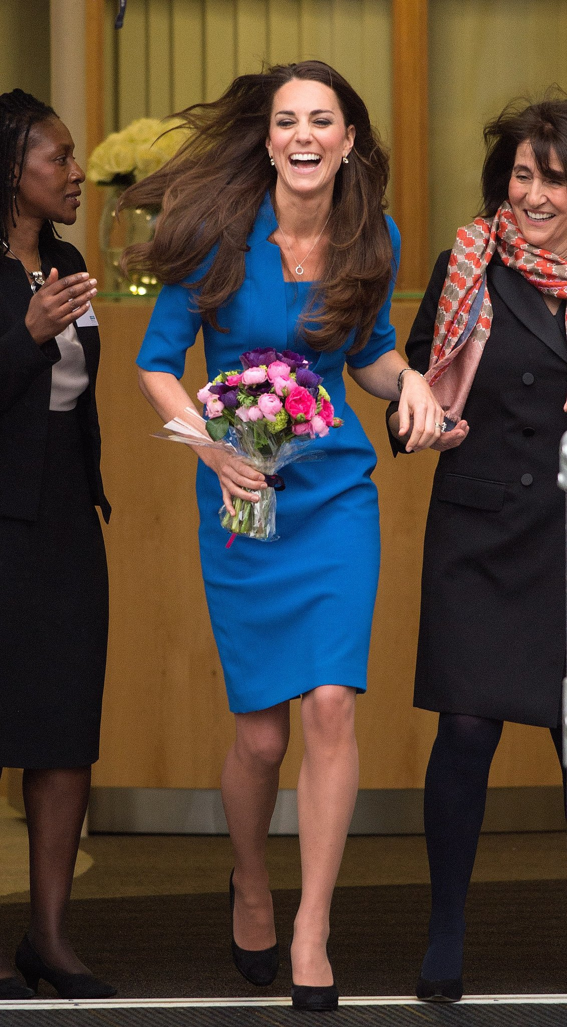 Kate laughed off a gust of wind when she visited the ICAP Art Room Opening at Northolt High School in London in February 2014.