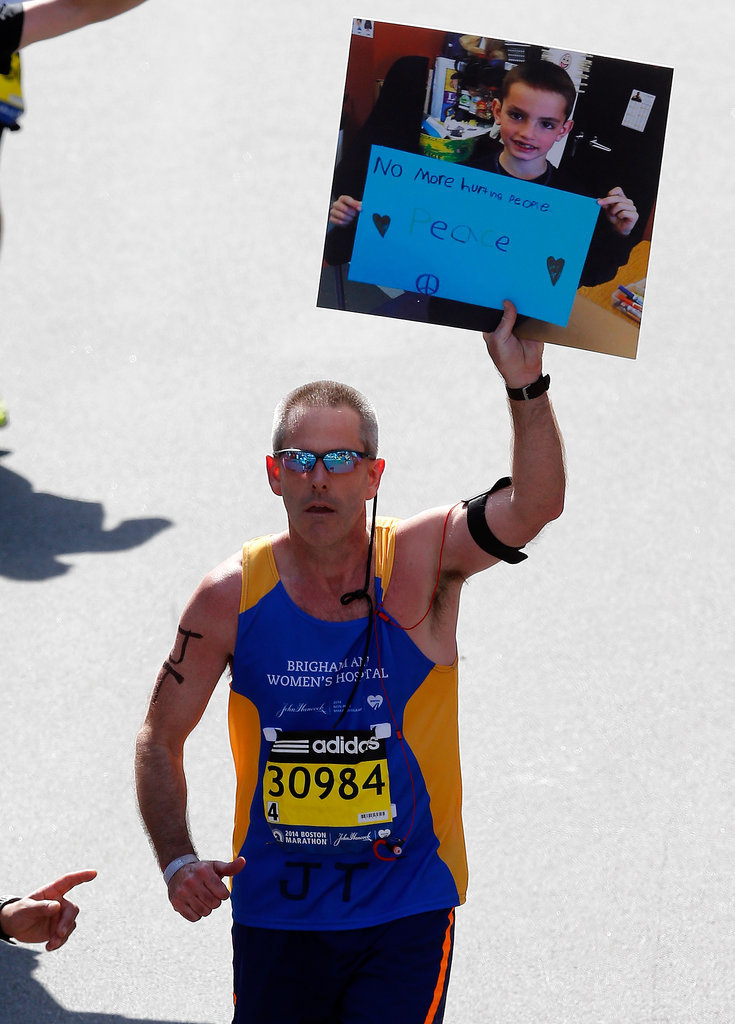 "One runner held up the iconic picture of Boston Marathon bombing victim Martin William Richard with a sign that read, ""No more hurting people. Peace."""