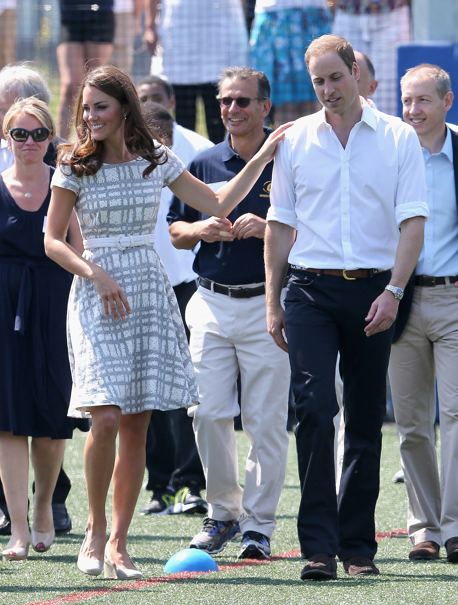 Kate Middleton put a hand on Prince William's shoulder while they visited Bacon's College in London in July 2012.