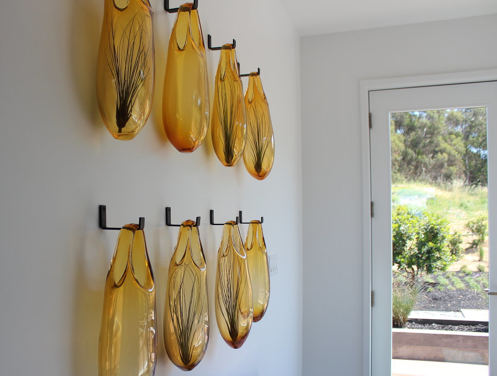 Rows of sculptural SkLO vases hang in one of the home's entryways.