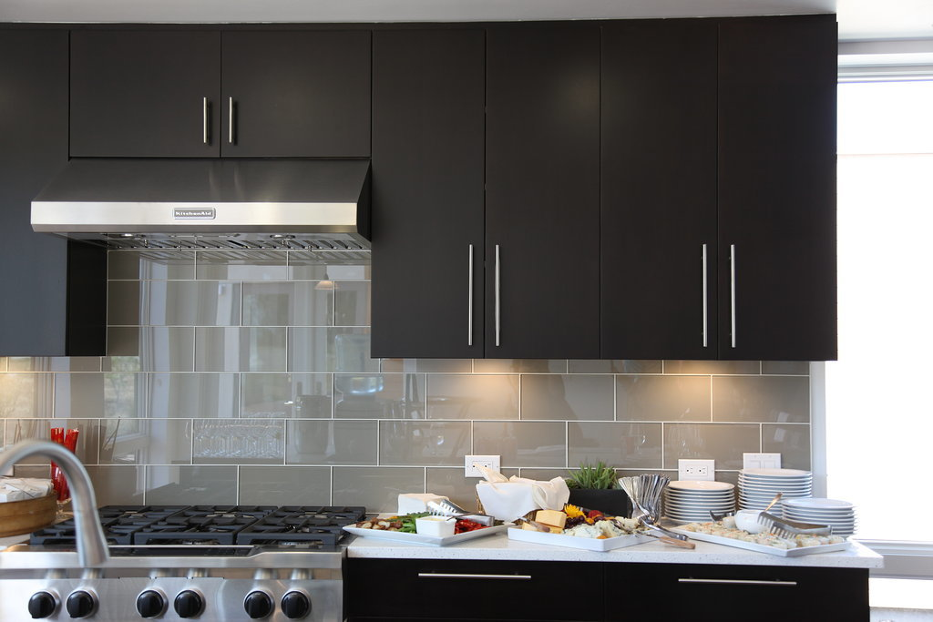 Sleek gray tiles and cabinetry give the kitchen a clean, modern look.  Photo: Chi Chau