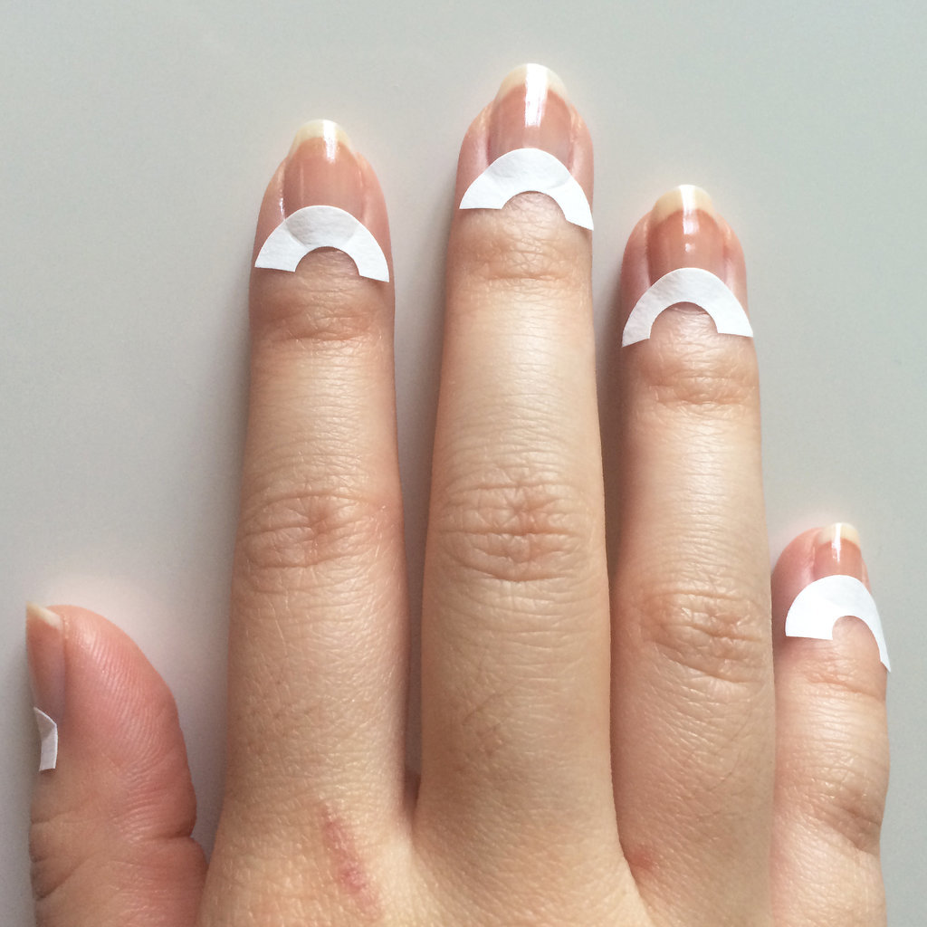 After applying your base coat, let it dry for a few minutes. Next, cut paper reinforcements in half (or you can just use whole ones) and place them at the base of your nails. This will create the half-moon shape of your manicure.